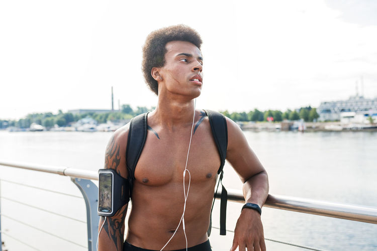 Thoughtful shirtless male athlete standing on promenade in city