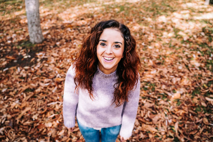Portrait of smiling woman standing in autumn leaves