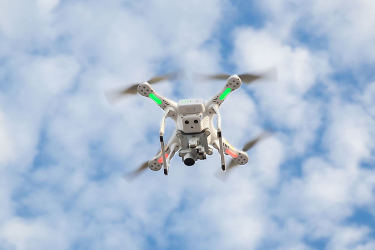 Low angle view of drone flying in cloudy sky