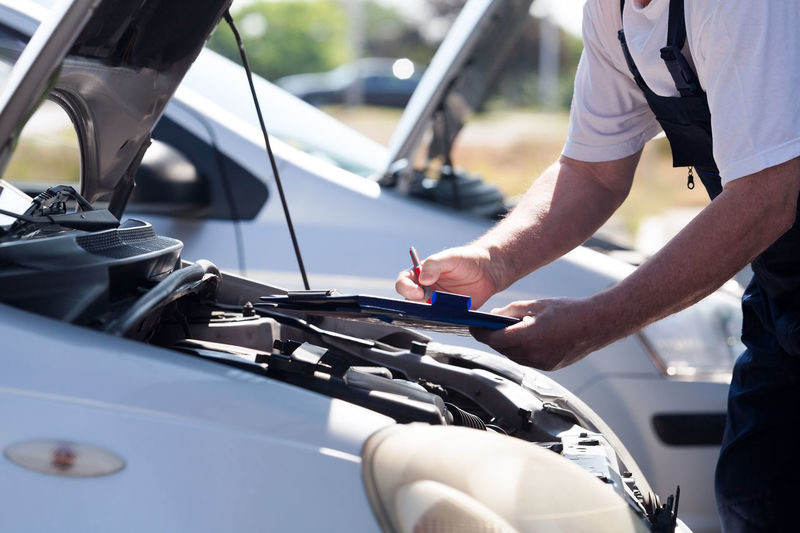 Midsection of man working while standing by car