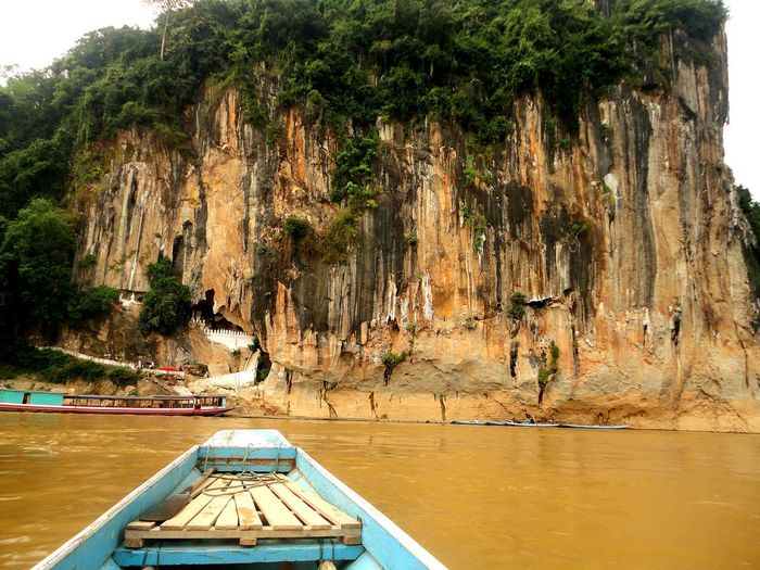 Boat on mekong river against pak ou caves
