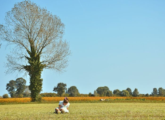 Girl sitting on grassy field against clear sky