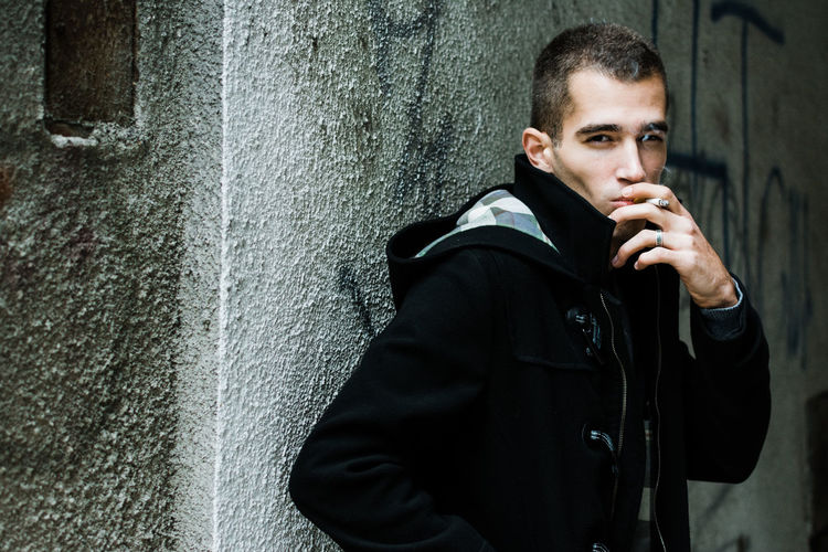Young man smoking while standing against wall