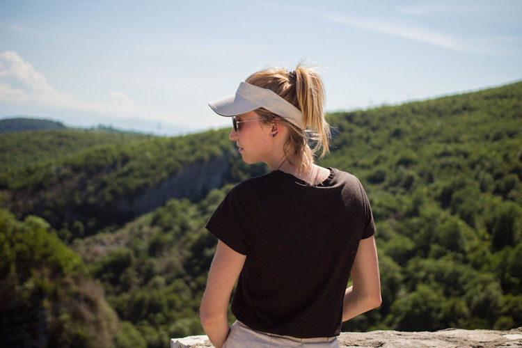 Woman wearing cap standing on field against mountain