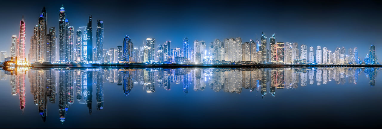 Panoramic view of illuminated buildings by sea against blue sky