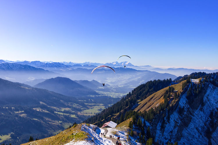 Distant view of people paragliding over mountains against clear sky