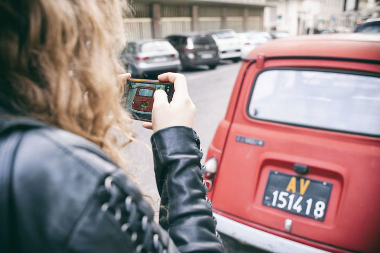 Rear view of woman using mobile phone in city