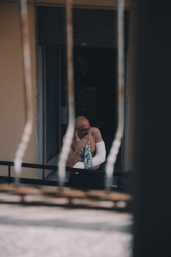Portrait of man photographing through window