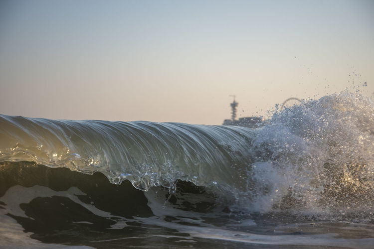 Close-up of waves splashing on shore against clear sky