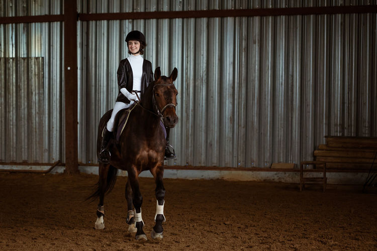 Young woman in special uniform and helmet riding horse. equestrian sport