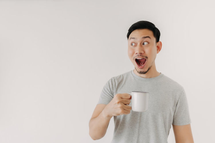 Portrait of mid adult man holding coffee cup against white background