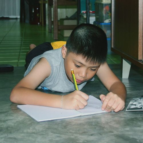 Boy Drawing In Book At Home