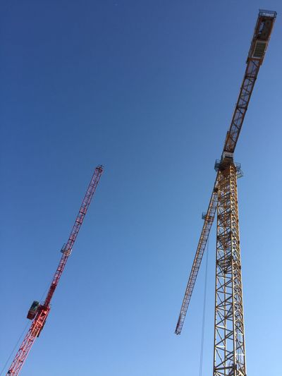 Low angle view cranes against clear blue sky