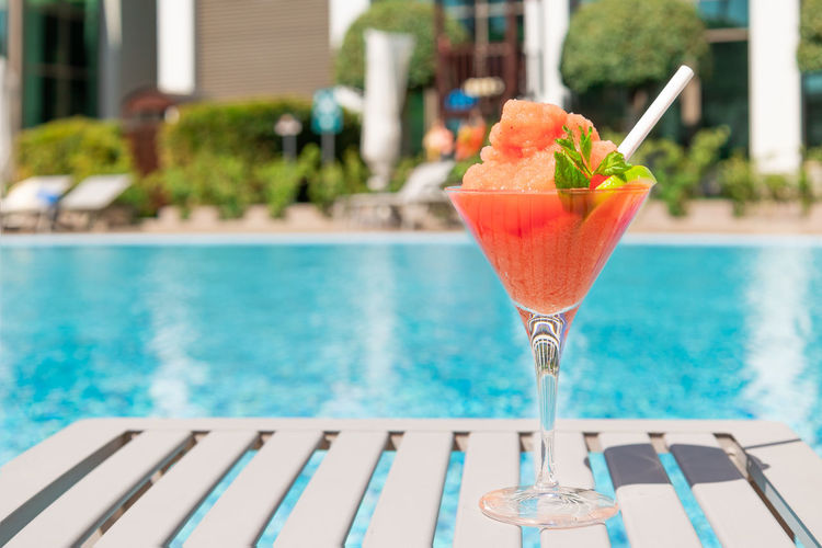 Close-up of drink on swimming pool