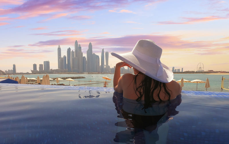 Beautiful young woman with a white hat in the infinity pool enjoyed the view of the skyline Dubai Marina at the sunset Architecture Sky Built Structure Hat City Water One Person Sunset Leisure Activity Lifestyles Rear View Standing Nature Cityscape Building Clothing Office Building Exterior Skyscraper Modern Looking At View Outdoors Dubai Woman Vacations Travel