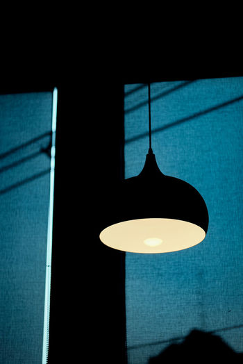 Low angle view of illuminated light bulb on wall