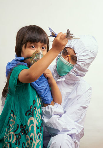 Doctor with girl wearing mask against white background
