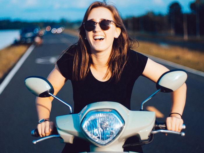 Smiling young woman sitting on motor scooter at road