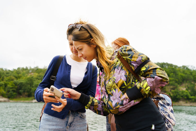 Young woman using phone while standing against sky