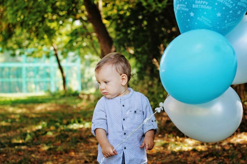 Cute baby boy with balloons standing against trees