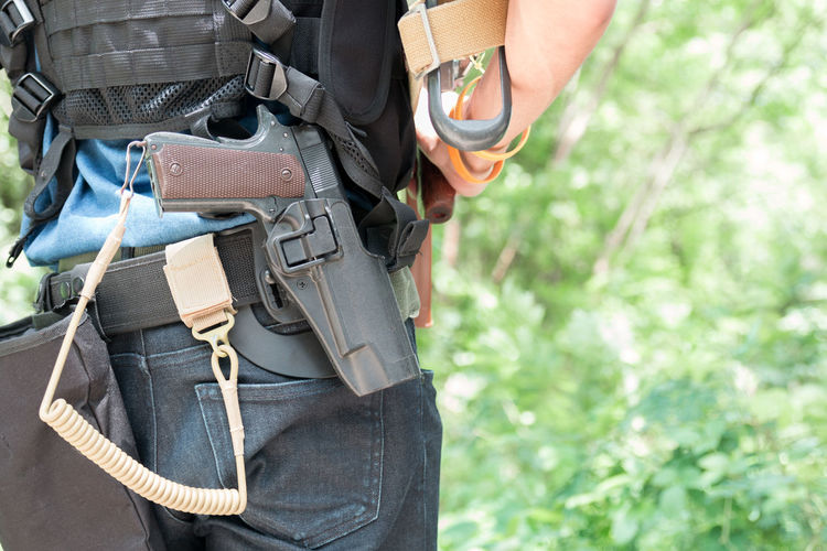 Midsection of police man with guns standing in forest