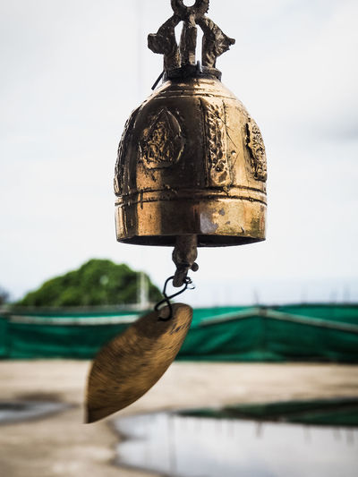 Close-up of golden bell hanging against sky