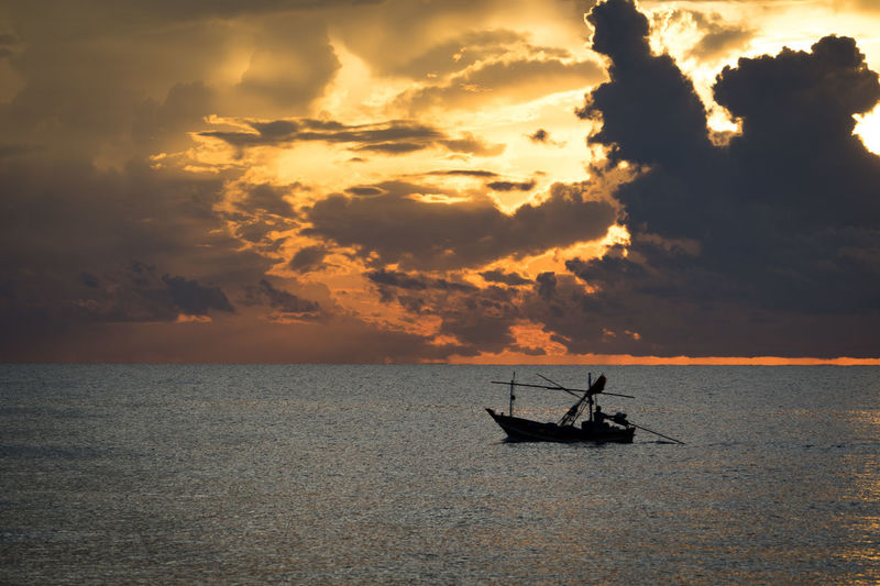 Silhouette man sailing in sea against sky during sunset