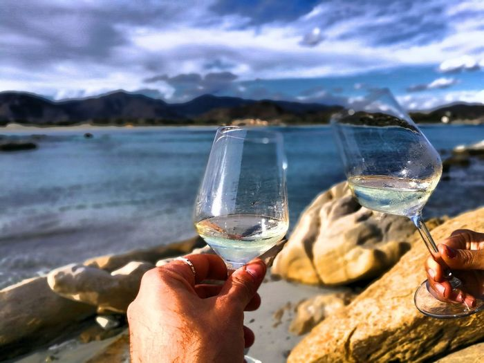 Cropped hands toasting wineglasses by sea