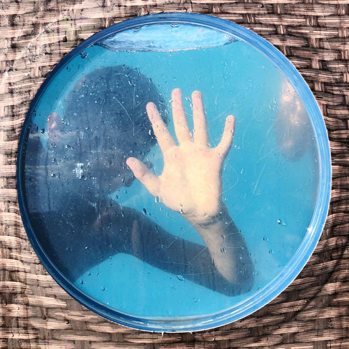 Close-up of hand on glass at swimming pool