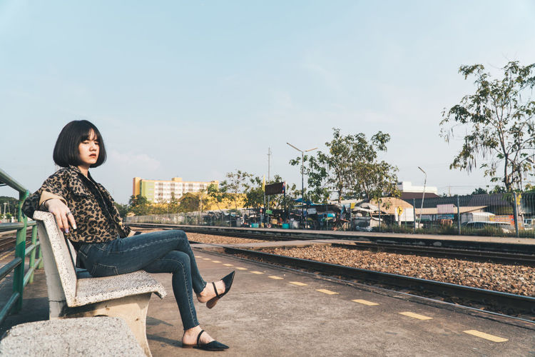 Full length of woman sitting on bench at railroad station platform