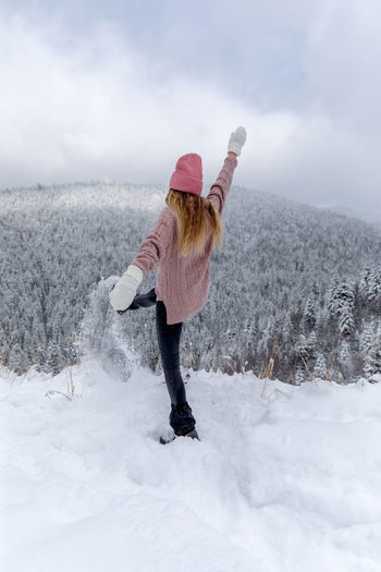 Woman standing on snow covered land against sky