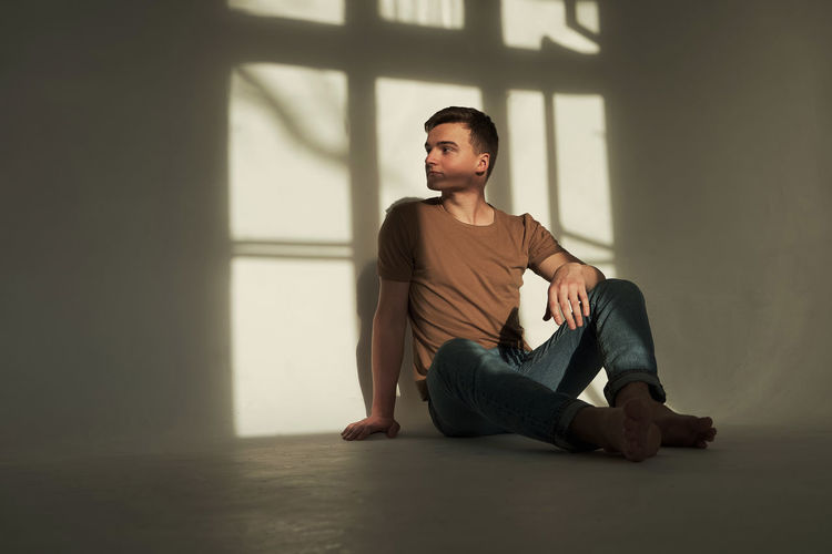 Young man looking away while sitting on window