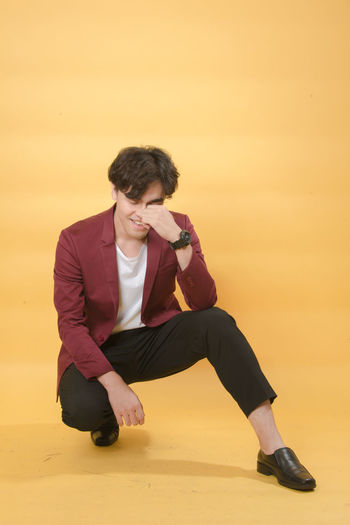 Full length of young man looking away while sitting on orange sunset