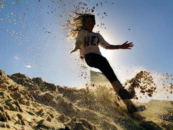 Woman jumping on sand against sky