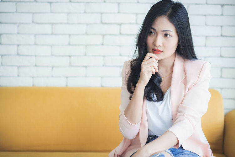 Beautiful young woman sitting against wall