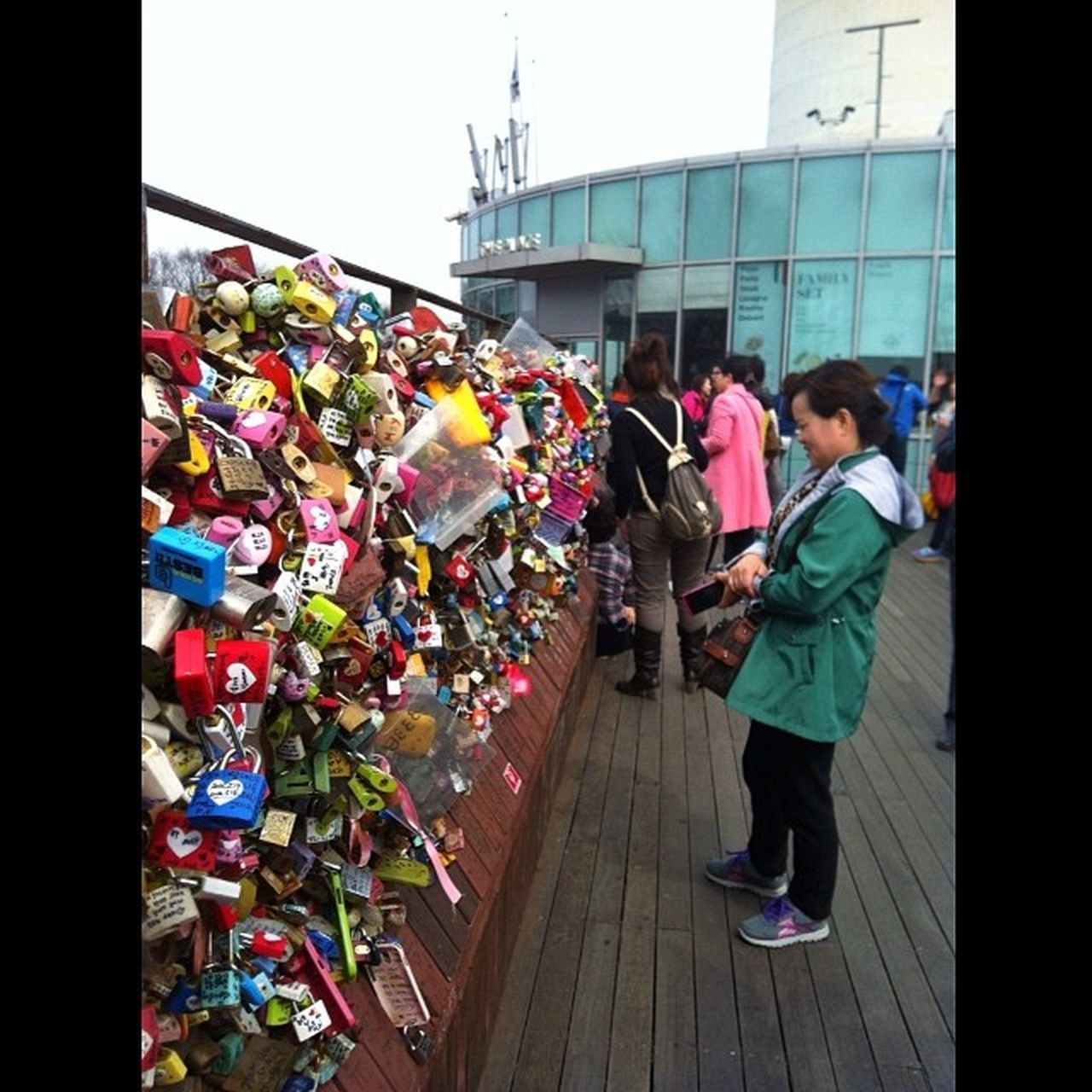 real people, railing, multi colored, architecture, built structure, day, outdoors, variation, bridge - man made structure, padlock, building exterior, men, love lock, full length, city, people
