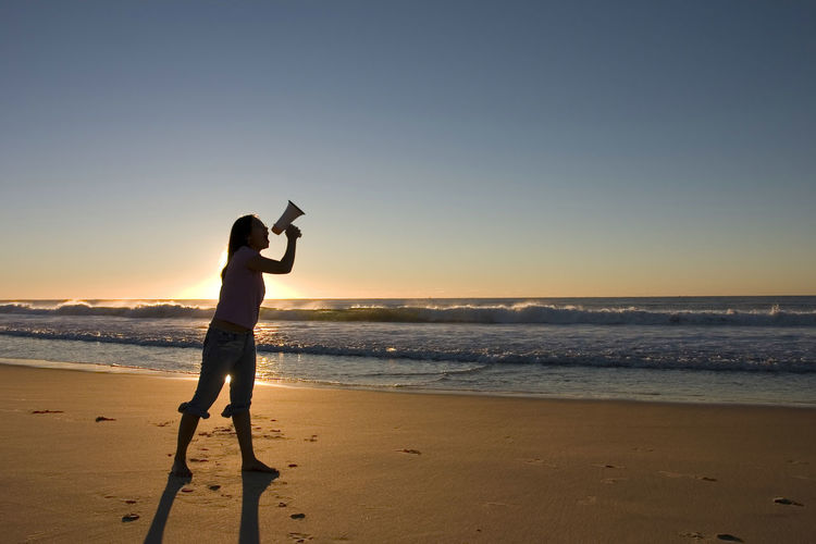 Side view of mid adult woman standing at beach against clear sky during sunset