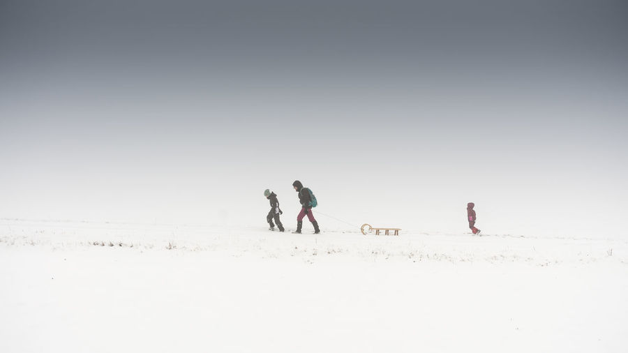 Family with sled on snow covered field against sky