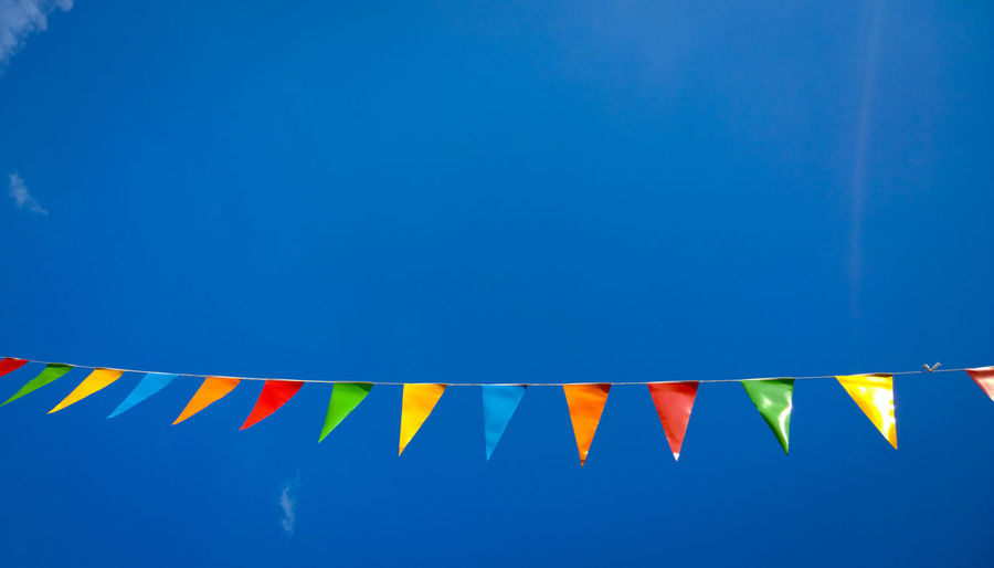 Low angle view of multi colored decorations against blue sky