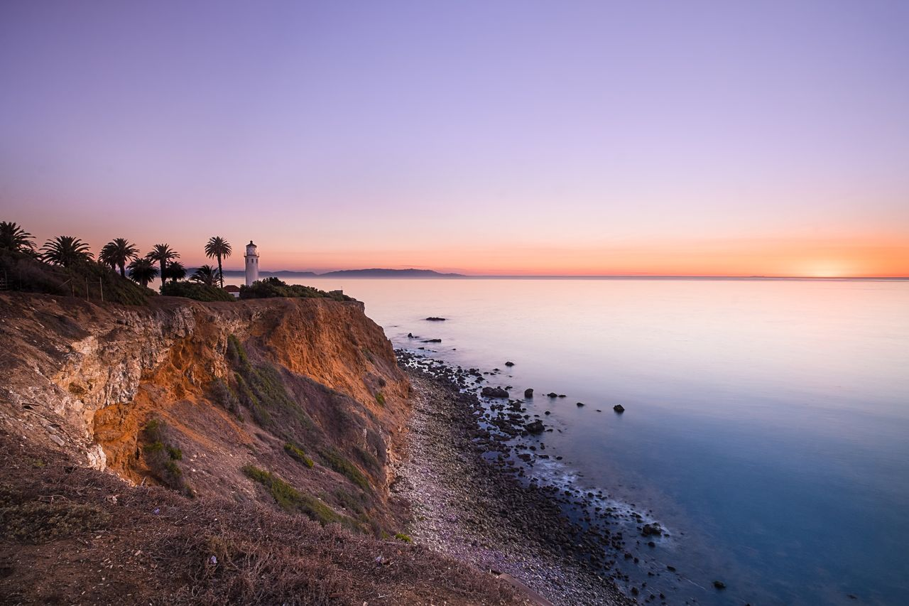 Scenic view of cliff by sea against sky during sunset