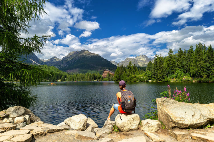 Man sitting on rock by lake against sky