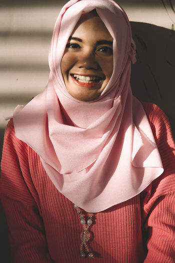 Close-Up Portrait Of Happy Woman In Hijab Standing By Wall