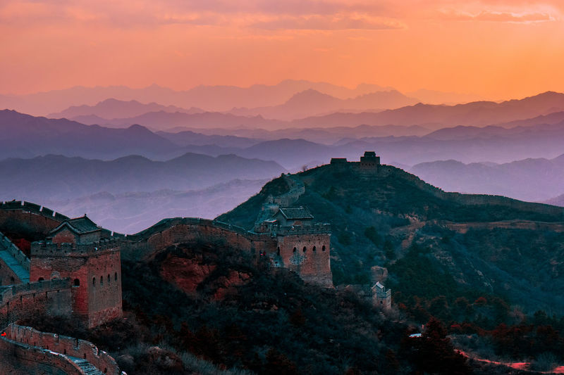 Scenic view of great wall of china on mountain against sky during sunset