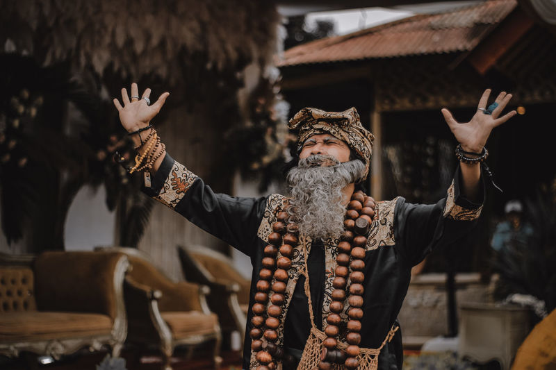 Man wearing traditional clothing gesturing while standing outdoors