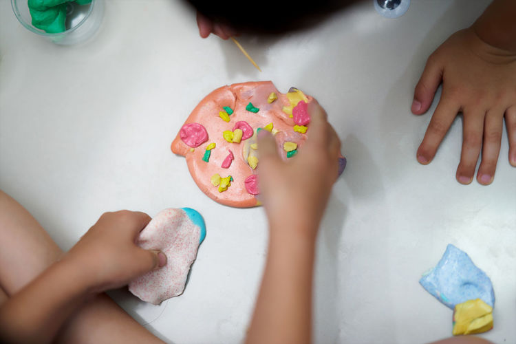 High angle view of siblings making craft product on floor
