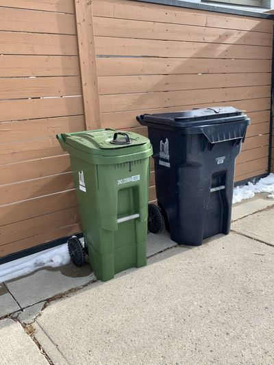 Garbage bin on footpath against wall