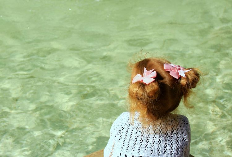 Rear view of girl sitting by water