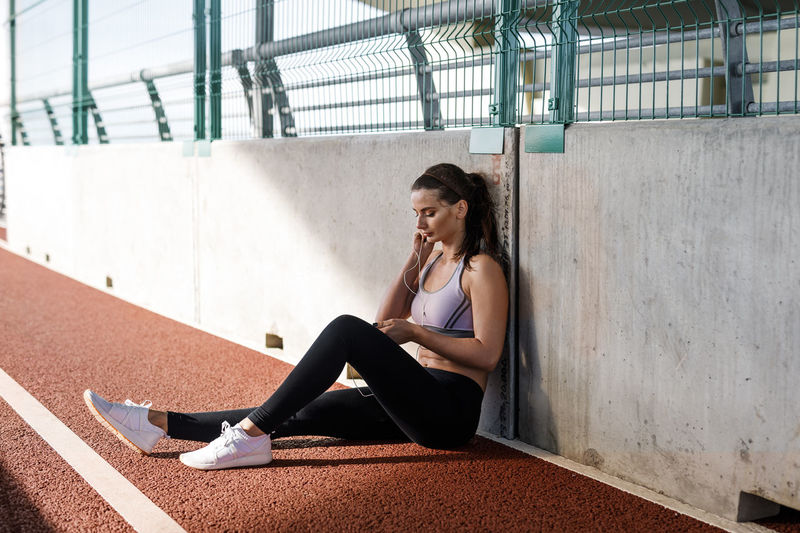 Young Woman Sitting On Running Track