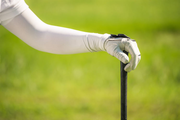 Cropped Hand Of Golfer With Golf Club At Course