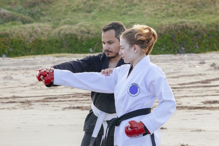 Coach teaching karate to teenage girl at bach